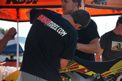 A pit crew member from Team Malcolm Smith/Norco Tires works on one of the motorcycles.