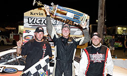 Austin Hill hoists the massive Kevin Whitaker Chevrolet 140 race winner trophy over his head in victory lane at the ½ mile semi-banked oval of Greenville Pickens Speedway in South Carolina
