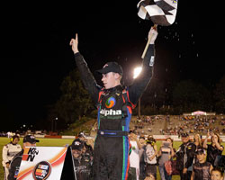 Ben Rhodes stands atop the Alpha Energy Solutions Chevrolet Impala waving the checkered flag after his victory at Bowman Gray Stadium in North Carolina