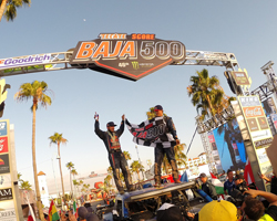 Bryce Menzie and co-pilot Pete stand atop the Red Bull sponsored Trophy Truck and celebrate their third Baja 500 overall victory
