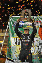Driver Jason Meyers hoisting a 1st place trophy in Victory Lane.