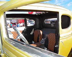 Custom upholstery, custom sheet metal interior, and the beautiful black and Scion Xb gold patina paint scheme of the Hogie Shine Rat Rod.