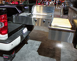 A Solaire 27 grill slides out on a custom system from the 1794 Edition Tundra's bed