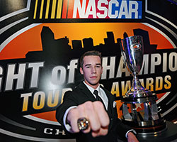 2014 NASCAR K&N Pro Series East champion Ben Rhodes poses in front of the championship trophy