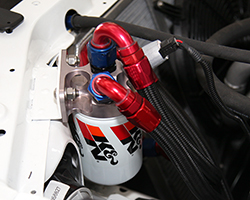A CV Products remote oil filter adaptor is used to relocate K&N Wrench-Off Oil Filter number HP-1018 on the Ford Racing Mustang RTR
