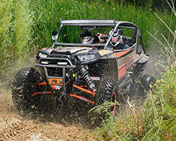 """A 2014 Polaris RZR XP 1000 has 16"""" of travel out front, 18"""" in the rear, and 13.5 inches of ground clearance to tackle almost any terrain"""