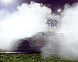Sergio Pena celebrates his NASCAR K&N Pro Series East race win at Columbus Motor Speedway with a triumphant cloud of white smoke