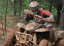 Angela Horn goes through mud, over rocks and does not stop in the pit area during quad races in her Honda 400EX, photo by Stacie Siegers