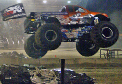 Iron Warrior flies the K&N flag as Trey Myers flies over car stacks in the wheelie contest