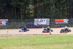 Racers screaming around a sweeping left-hand turn.