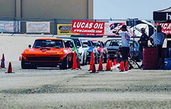 Greg Thurmond in his 1965 Candy Tangerine Corvette with Richard Trujillo in his Deliciously Lime '69 Mustang at Hotchkis Cup Autocross Challenge
