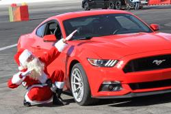 Santa posing with his 2017 Ford Mustang 5.0L at Orange show speedway